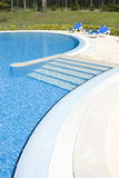 Swiming Pool. Detail of a swiming poll with blue water and 3 chairs Stock Photo