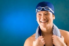 Swimmer. Portrait of happy sportsman in swimming cap and goggles over blue background Royalty Free Stock Images