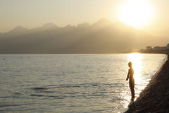 The Swimmer. Young man in rays of the setting sun ready to enter the water, Mediterranean Sea, Konyaalti beach, Antalya, Turkey Stock Images