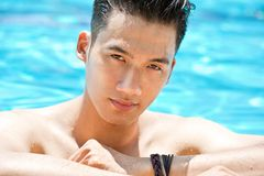 Swimmer. Wet Asian man looking at camera in swimming pool Stock Images