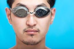 Swimmer. Portrait of the guy of asian appearance in swimming glasses on a blue background Royalty Free Stock Images