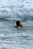 Swimmer. Lone swimmer ventures out into the waves stock images