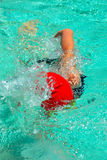Swimmer. A young caucasian active swimmer athlete with cap and costume swimming in the pool water outdoors Royalty Free Stock Images