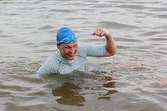 The swimmer in a blue cap rejoices to a victory Royalty Free Stock Photography