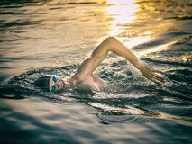 Swimmer breathing during swimming crawl. In the sea at sunset royalty free stock photography