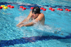 Swimmer in cap breathing performing the breaststroke Royalty Free Stock Photo