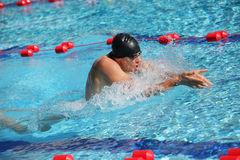 Swimmer in cap breathing performing the breaststroke Royalty Free Stock Photography
