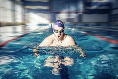 Swimmer in cap breathing performing the butterfly Royalty Free Stock Photography