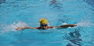 Young boy swimmer in pool,butterfly stroke. Swimmer in cap breathing performing the butterfly stroke Royalty Free Stock Photos