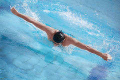 Swimmer in cap performing the butterfly stroke Royalty Free Stock Photography