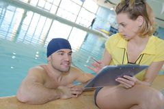 Swimmer and coach discussing by pool Royalty Free Stock Image