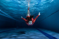 Swimmer dives into the water. Swimmer dives into the pool, wearing a red dress Royalty Free Stock Images