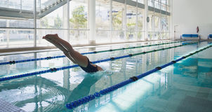Swimmer diving into the pool at leisure center. Side view of a fit swimmer diving into the pool at leisure center Stock Photo