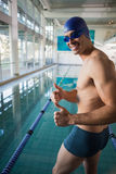 Swimmer gesturing thumbs up by pool at leisure center Royalty Free Stock Image
