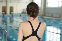 Swimmer girl with neck pain before swimming moment standing near poolside. Sport injury concept Stock Photography
