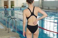 Swimmer girl with pain in the small of the back. Young sportsman woman with back pain Royalty Free Stock Photo