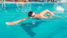 Swimmer in glasses swims in indoor swimming pool Royalty Free Stock Photos