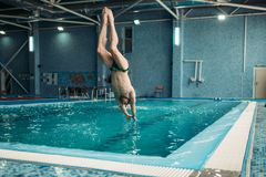 Swimmer in goggles jumping from the tower. Into the water, training in swimming pool, healthy activity. Underwater sport Stock Photography