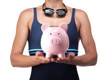 Swimmer holding a piggy bank Royalty Free Stock Images