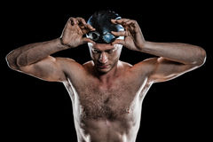 Swimmer holding swimming goggles. Swimmer looking down and holding swimming goggles on black background stock photos