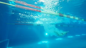Swimmer jump into swimming pool slow motion. Man swimmer dives a swimming pool. Male swimmer at start jumps into water in pool underwater view. Close up man stock video