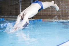 Swimmer jumping headfirst. Male swimmer is diving head first from the edge of an indoor swimming pool  - focus on the right arm Royalty Free Stock Image