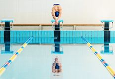 Swimmer jumping from starting block. Young muscular swimmer jumping from starting block in a swimming pool stock photo