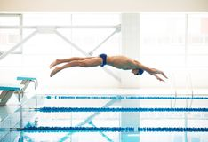 Swimmer jumping from starting block Royalty Free Stock Photos