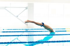 Swimmer jumping from starting block Stock Photography