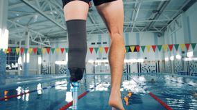 Swimmer with a leg prosthesis training near a pool, bionic equipment. 4K stock video