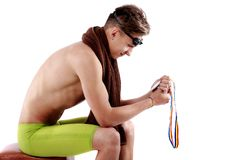 Swimmer looks at medal Stock Photo