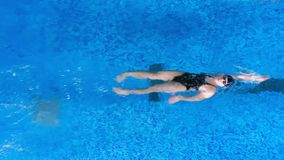 A swimmer moves on her back underwater before moving up. A female swimmer moves on her back underwater before starting back breaststrokes stock video footage