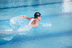 Swimmer  performing the butterfly stroke,profile. Swimmer in competition swimwear and cap breathing performing the butterfly stroke,profile and back view Royalty Free Stock Photo
