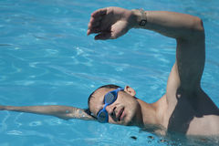 Swimmer performing crawl stroke. Male Swimmer performing the crawl stroke at blue water pool Stock Photography
