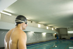 Swimmer by Pool. Male swimmer with cap and goggles on standing by a pool with a serious look on his face. Horizontally framed photo Stock Photos