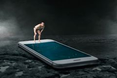 Swimmer ready to dive into the phone screen. Swimmer ready to dive into the pool is made from large phone screen. Always be in touch or online addiction concept Royalty Free Stock Images