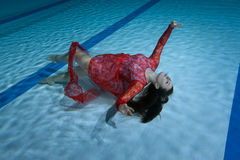 Swimmer in a red dress. Swimmer in a red dress poses under the water showing figures Stock Image
