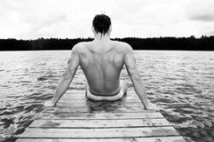 Swimmer resting by lake. Rear black and white view of muscular swimmer resting on pier by lake Royalty Free Stock Image