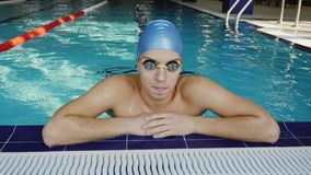 The tired swimmer rests in the pool. Swimmer resting lying on the side of the pool. Young male swimmer in the pool. The tired swimmer rests in the pool stock footage