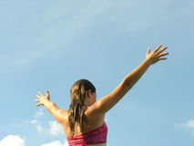 Swimmer and sky. A young girl swimmer spreads her arms to the open blue sky Royalty Free Stock Photography