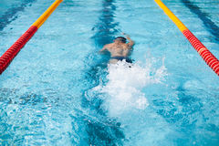 Swimmer splash after diving in the pool during contest Stock Images