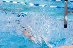 Swimmer Splashes At Backstroke Start. A swimmer makes a large splash as the start a backstroke race Stock Photos