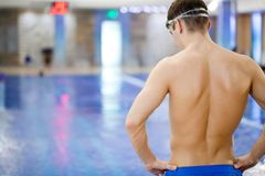 Swimmer. Sporty muscular man standing in front of the pool. Unrecognizable Royalty Free Stock Photos