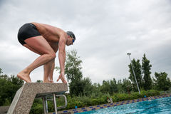 Swimmer standing on starting block at swimming pool. Man standing on starting block at public swimming pool ready to jump Royalty Free Stock Images