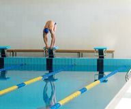 Swimmer standing on starting block Stock Photos