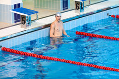 Swimmer standing in water of swimming pool Royalty Free Stock Image
