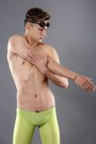 Swimmer stretching. Studio shot over gray. Royalty Free Stock Images