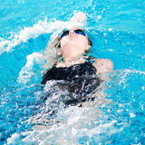 Swimmer in swim meet doing backstroke Royalty Free Stock Photography