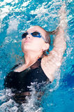 Swimmer in swim meet doing backstroke. Teenage girl swimming in swim meet doing backstroke Stock Photo