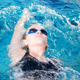 Swimmer in swim meet doing backstroke Stock Images